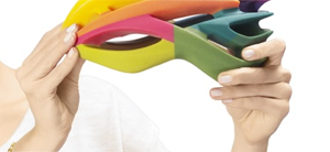 A person holding a multi-colored bike helmet that was made with the Stratasys Connex3, using PolyJet materials