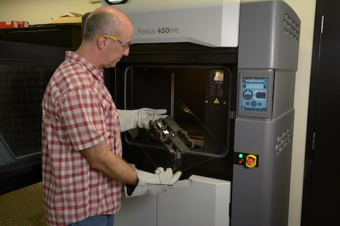 Rob Humphries removing an FDM Nylon 12CF part from Thule's 3D printer.