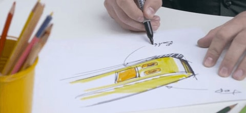 a person sketching out ideas with paper and colored pencils